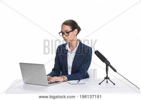 Attractive Female Newscaster Sitting At Table With Laptop, Notepad And Microphone, Isolated On White
