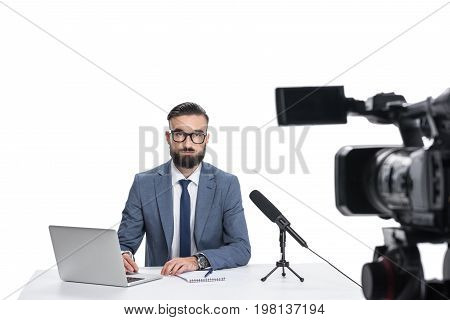 Male Newscaster Sitting At Table With Laptop, Notepad And Microphone And Looking At Camera, Isolated