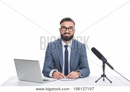 Happy Male Newscaster Sitting At Table With Laptop, Notepad And Microphone, Isolated On White