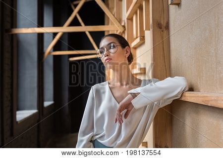 Charming Stylish Businesswoman Posing In White Blouse And Eyeglasses While Looking Away