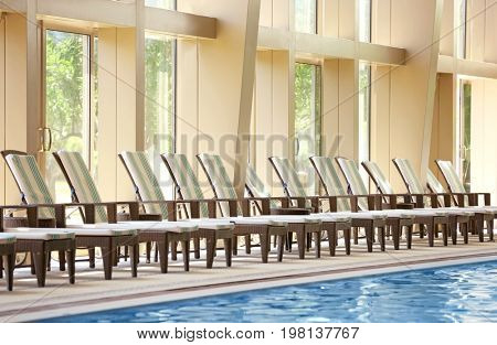 Chaise lounges near swimming pool in luxury hotel