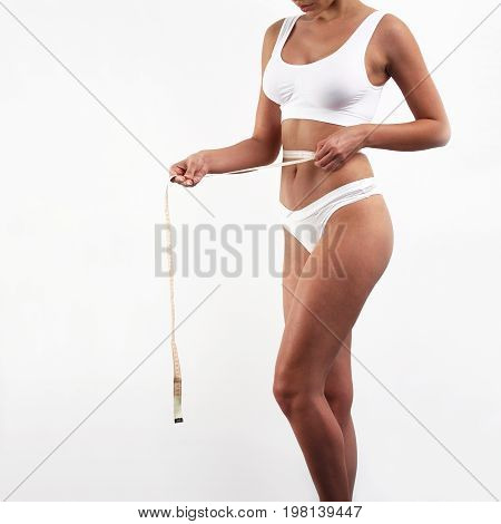 Woman measuring her waist with a measuring tape checking her weight loss progress