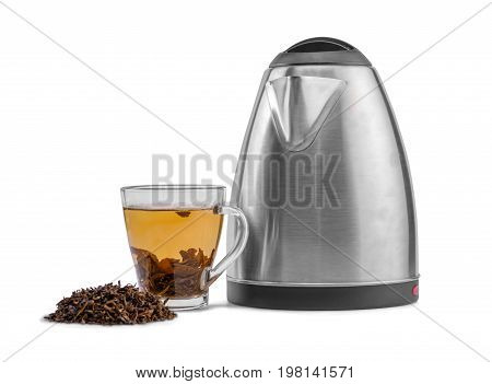 A close-up of a glass tea cup full of green tea and a shiny metal kettle on a white background. A cup of hot beverage, modern utensil and a heap green tea leaves. Winter organic beverage. Healthy tea