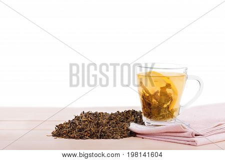 A close-up of a glass cup full of green tea isolated on a white background. A cup with liquid, lemon next to heap of green tea leaves on a rose table-napkin and light wooden table. Natural beverage.