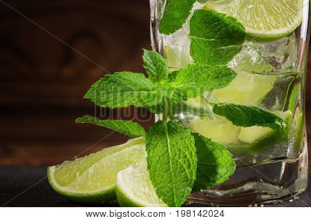 A close-up picture of a glass of a green mojito on a wooden background. Sliced green lime, peppermint leaves and ice cubes next to an alcoholic mojito. A mojito with rum or liquor in a big glass.