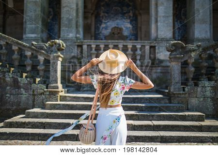 Back View Of A Stylish Female Tourist Admires Of A Beautiful Architectural Building During Walking I