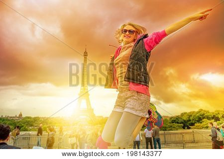 Happy tourist woman jumping with Tour Eiffel on background. Lifestyle traveler enjoing at Eiffel Tower from Place du Trocadero, icon of Paris, France. Freedom and travel concept. Sunset dramatic sky.