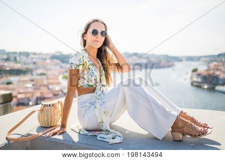 Young Pretty Woman Sitting On The View Point In Front Of The Douro River And Dom Luis I Bridge In Po