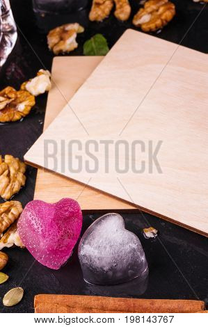 Cute composition of wooden postcards on a black table background. Walnuts, cinnamon sticks, ice hearts and green leaves next to a light brown invitation card. Creativity, romance concept. Copy space.