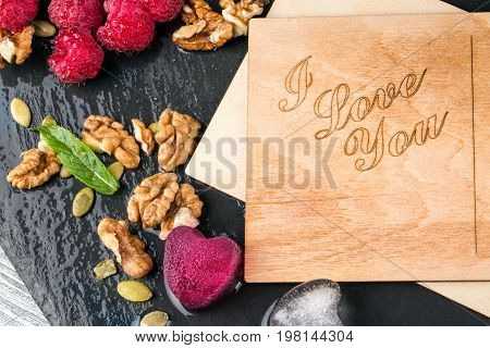 A top view of a beautiful composition of romantic postcards, fruity hearts, walnuts and leaves on a black wooden background. Pink raspberries and ice hearts next to a love note. Romance concept.