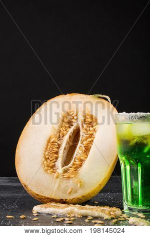 Close-up of a beautiful composition of deliciously cut melon and a glass of alcoholic drink on a saturated black background. Juicy, ripe, raw melon and refreshing summer beverage with ice. Copy space.