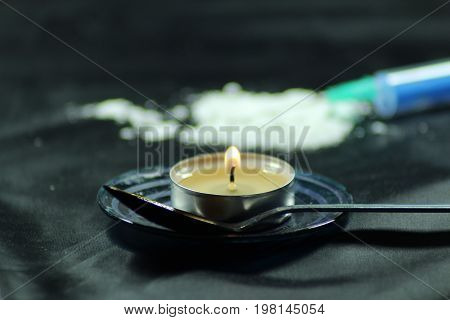 Heroin/ Heroin, candle, syringe and tea spoon on black background.