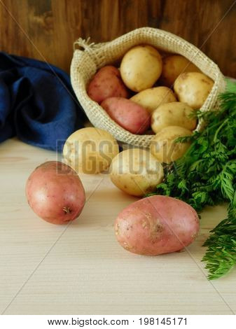 Potatoes are scattering out of a sack on a wooden background