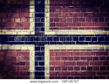 Faded Norwegian flag on an old brick wall background with a dark vignette