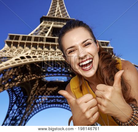 Smiling Young Woman Showing Thumbs Up In Front Of Eiffel Tower