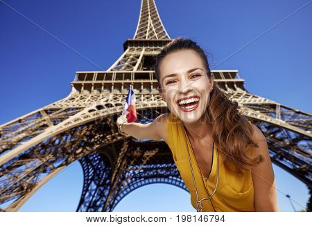 Touristy without doubt but yet so fun. Portrait of happy young woman rising flag against Eiffel tower in Paris France