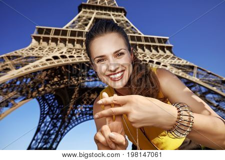 Smiling Woman Showing Hashtag Gesture Against Eiffel Tower