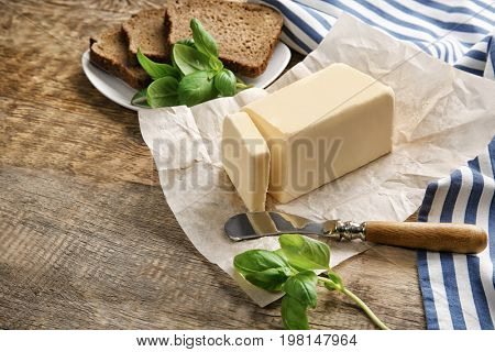 Piece of unwrapped butter, knife and plate with sliced bread on wooden table