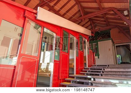 Ropeway summit station with red cable car - roof and stairs at entrance / exit