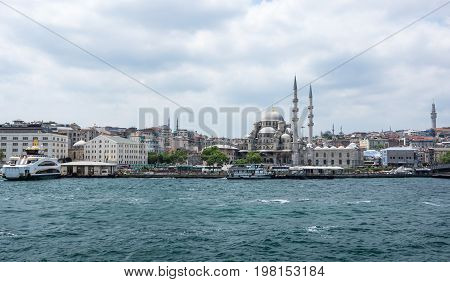 ISTANBUL TURKEY - JUNE 25 2015: View on New Mosque and embankment in Eminonu Istanbul Turkey