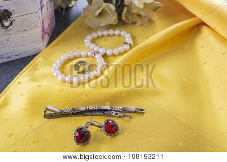 Bracelets and earings and ring on the yellow background