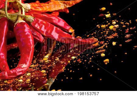 Red chili peppers and chili flakes on a black background with reflection and copy space