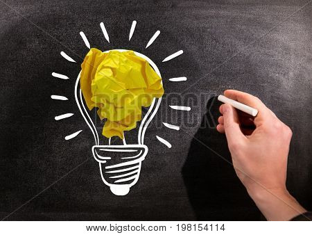 Digital composite of Hand drawing light bulbs on blackboard with chalk and crumpled paper balls on blackboard