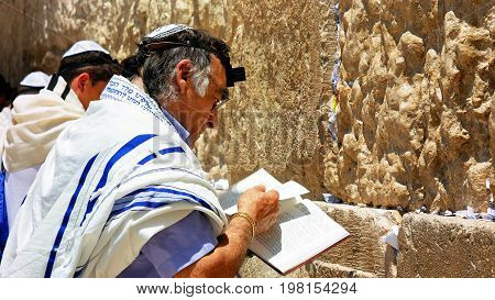 Jerusalem, Israel - May 25, 2017: Jew haredi pray at the Western Wall also known as Wailing Wall or Kotel in Jerusalem. The Western Wall is the most sacred place for all jews and jewish in the world.