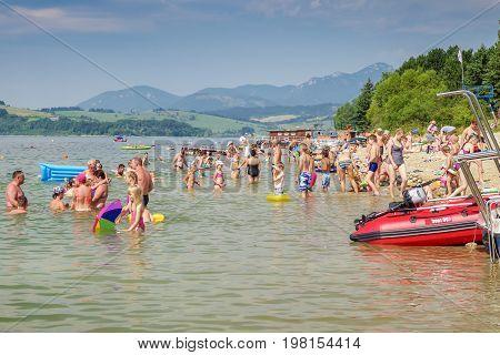 LiPTOVSKY TRNOVEC SLOVAKIA - AUGUST 2: People relaxing and sunbathing on shore of water reservoir Liptovska Mara on August 2 2017 in Liptovsky Trnovec
