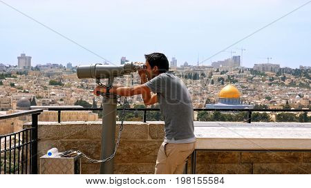 Jerusalem, Israel - May 25, 2017: Tourist looks in binoculars tower viewer at the Jerusalem Old City view. Mount of Olives is a famous Holy Land place and it has a fantastic view to the Old Jerusalem