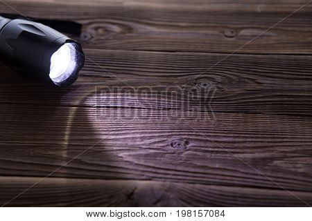 Wooden background with flashlight on