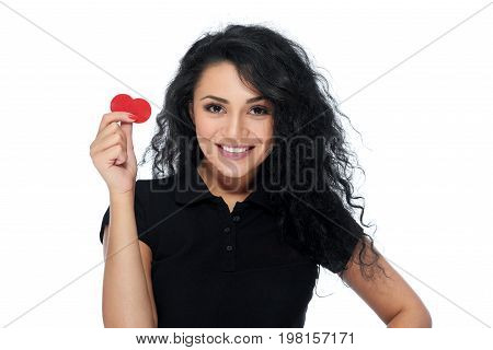 Beautiful young woman with dark curly hair smiling playfully to the camera holding two casino tokens in her hand isolated on white game gambling croupier concept.