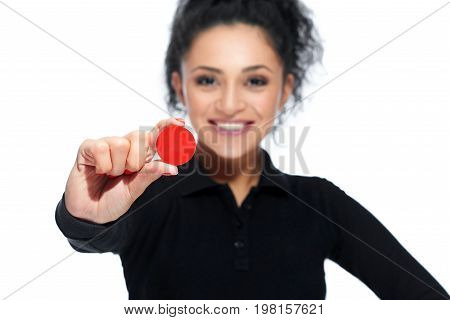 Selective focus on a red casino token in the hand of a beautiful dark haired woman copyspace gambling playing game luck offering concept.