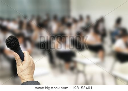 Education Background with copy space shown teacher hold microphone in hid hand to lecture for his students in the classroom.
