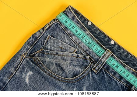 Top Part Of Denim Trousers Isolated On Yellow Background