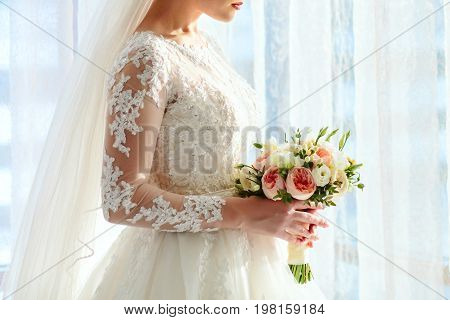 A beautiful bride is standing near the window and holding a wedding bouquet with white roses and peach peonies. Close-up indoor