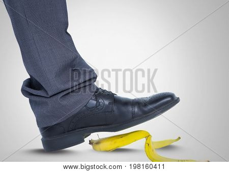 Digital composite of Man stepping on banana skin with black shoe