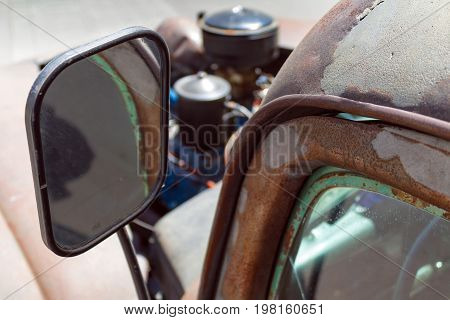 Vintage American rear view mirror and rusting door close up with a shallow depth of field