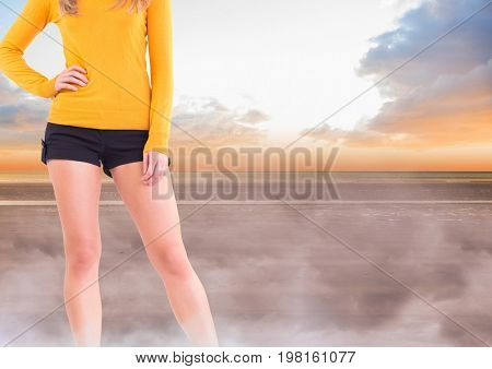 Digital composite of Sexy woman's legs in mystical landscape with yellow jumper