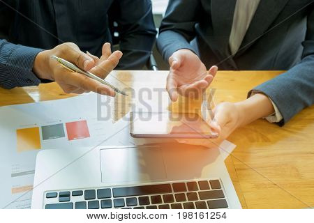 Two business people are consulting,Businessman holding pen in hand the other holds a tablet,Data graph and laptop placed on the desk.