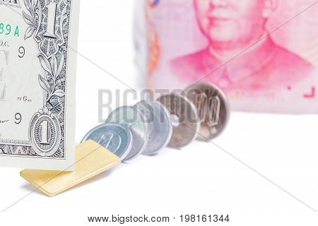 Focus on one US dollar bill with blurred Chinese yuan banknote and Japanese yen coins on white background world economy concept.
