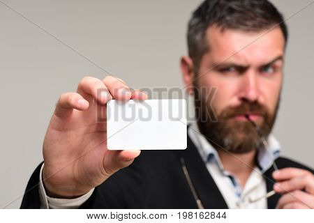 Man In Classic Suit With Thick Beard Holds White Card