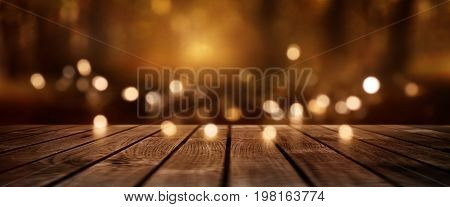 Festive luminous background with golden lights and empty rustic wooden table for christmas and advent