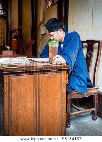 Shanghai, China - Nov 6, 2016: In the 600-year-old Old City God Temple. A Taoist priest in traditional clothing reading at a table with a small jug of tea in hand.