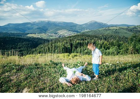 grandmother lying on the peak of the hill and enjoing the view, warm sunny day, little boy looking at her