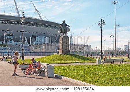 SAINT - PETERSBURG, RUSSIA - AUGUST 1, 2017: People on The Krestovsky Island near Sergei Kirov Statue. On the background is Krestovsky Stadium (Zenit Arena) by Kisho Kurokawa architect