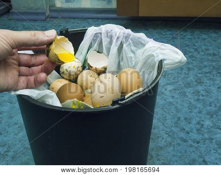 Human hand throwing bad egg into a rubbish bin filtered photo