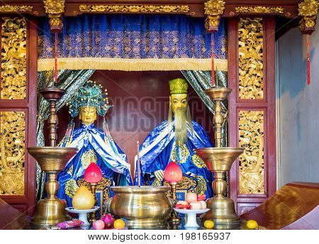 Shanghai, China - Nov 6, 2016: In the 600-year-old Old City God Temple. Old Taoist deities (male and female) depicted as heavenly couple placed together at an ornate altar.