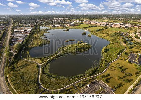 Aerial view of a lake and peninsula near a community center and townhomes with walking paths and bridge in The Glen, Glenview, Illinois.