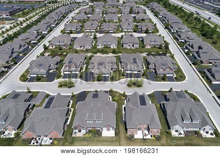 Aerial view of a townhouse complex in a semi-circular Chicago suburban neighborhood in summer.